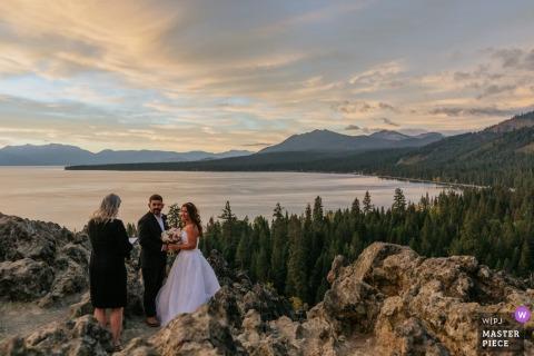 Fotografia di matrimonio a distanza in esterni in California da Tahoe City, CA che mostra gli sposi che ascoltano il loro officiante durante la cerimonia all'alba