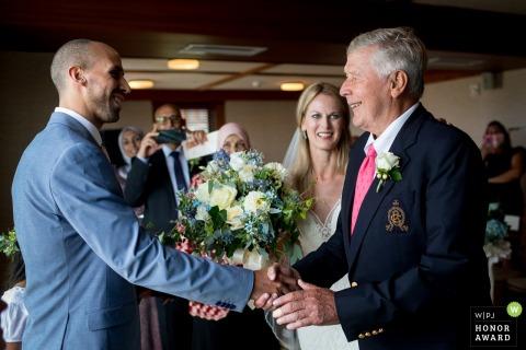 Zdjęcie ślubne z Rhode Island z ceremonii ślubnej w Westerly przedstawiające panny młode, tata ściskający dłoń stajennych