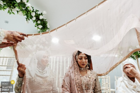 West Midlands wedding photographer created this image at a Private venue in Birmingham, UK of a Muslim bride with her mother and grandmother