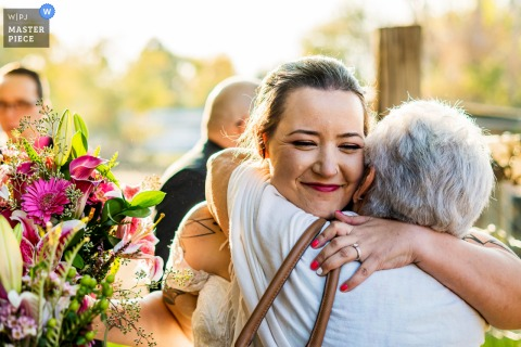 Colorado wedding photographer created this image from a Private home, Lafayette, CO as the bride hugs grandma after ceremony