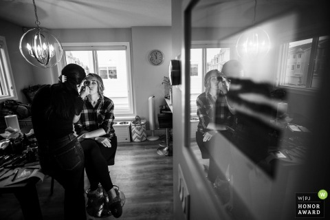 Alberta creative wedding photo of the Bride reflected in glass during makeup