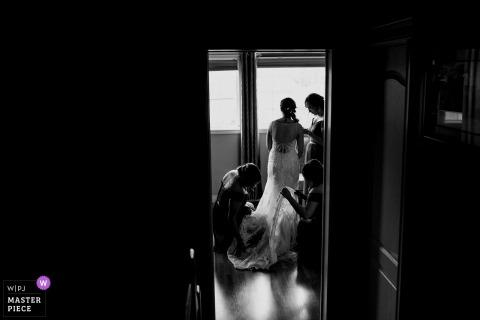 Trouwfoto Alberta van Home of the Bride gezien door deurkleding met bruidsmeisjes