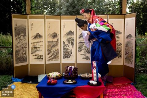 Washington wedding photo Parents Backyard Wedding che mostra lo sposo che porta la sposa intorno al tavolo durante la cerimonia coreana di Pyebaek