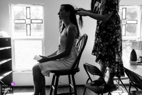 Immagine del matrimonio che mostra la sorella delle spose in piedi su una sedia per acconciare i capelli delle spose prima della cerimonia della chiesa ortodossa di Santa Elisabetta