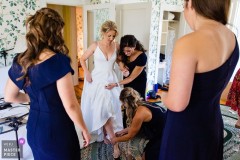 Bridesmaids help the bride put on her shoes at her Northeast Harbor Maine wedding in this real moment photo