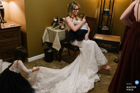L'immagine di una sposa di Schenectady, NY che indossa il suo abito da sposa tiene in braccio il suo bambino addormentato mentre una piccola fioraia raddrizza il suo strascico.