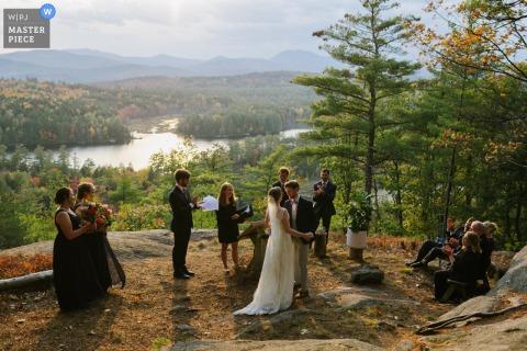 Forest Lake Camp a Chestertown, NY, immagine di una coppia che si abbraccia alla fine della cerimonia sul fianco di una montagna mentre il sole si abbassa nel cielo. La loro festa di matrimonio e i genitori li circondano.