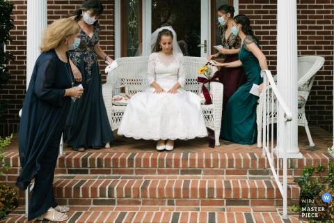 Immagine di una sposa seduta su una sedia di vimini in tranquilla contemplazione mentre aspetta di incontrare il suo sposo, mentre le sue donne membri della famiglia si stabiliscono intorno a lei a Long Island, NY