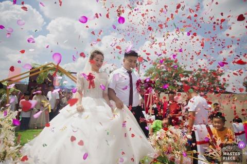 陕西婚礼照片显示花瓣和新来者在云层下的户外婚礼上很漂亮
