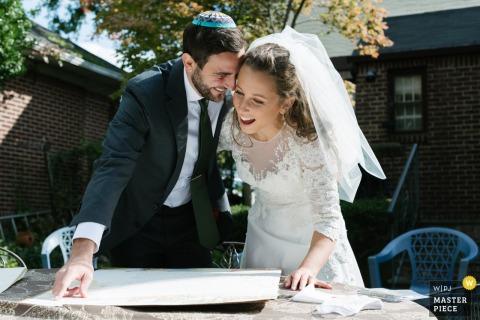 Long Island, NY immagine del matrimonio di una sposa e uno sposo che si stringono gioiosamente vicini mentre vedono per la prima volta il loro matrimonio ketubah.