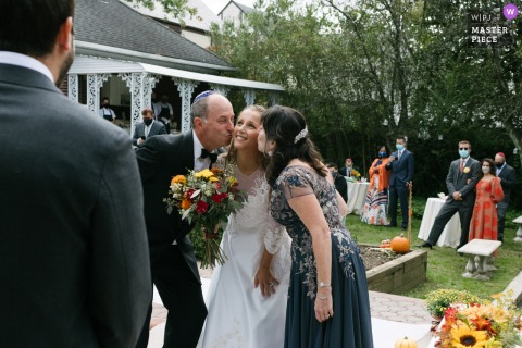 Photo showing a bride kissed on the cheek by her mother and father at the same time as they pass her to the groom at the start of a Long Island, NY outdoor wedding ceremony.