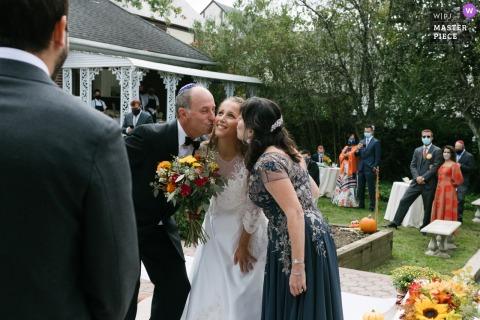 Foto che mostra una sposa baciata sulla guancia da sua madre e suo padre nello stesso momento in cui la passano allo sposo all'inizio di una cerimonia di matrimonio all'aperto a Long Island, NY.