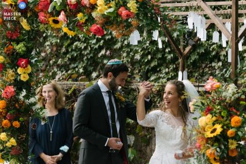 Zdjęcie przedstawiające pannę młodą i pana młodego z Long Island w stanie Nowy Jork radośnie trzymających się za ręce i świętujących podczas ceremonii ślubnej w otoczeniu kwiatów.