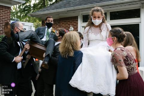 Immagine che mostra la sposa e lo sposo vengono sollevati su sedie per celebrare subito dopo la loro cerimonia di matrimonio a Long Island, NY