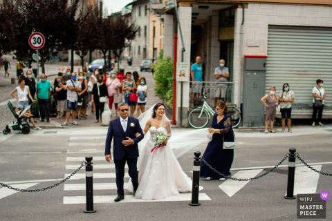 Fotografía de boda fuera de la Iglesia de San Andrea, Suisio (Bg) mientras la gente en la calle ve llegar a la novia