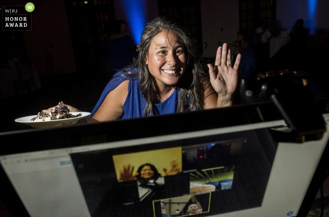 Arizona wedding guest waves to family members on Zoom during the reception at the Secert Garden Event Center in Phoenix