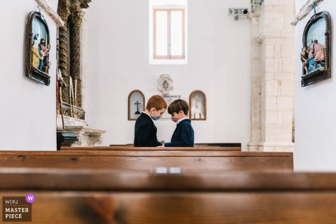 Puglia church wedding photography of 2 boys behind pews