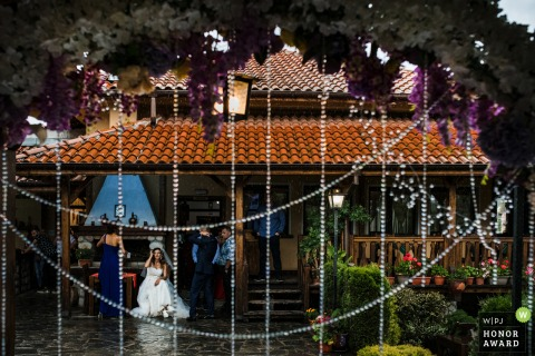 Momin Prohod wedding image of the bride sitting on the porch during a heavy rain just before the ceremony