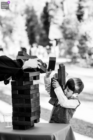 Incline Village, NV wedding photo showing a Jenga game going in an unexpected direction upon a child's head during a wedding reception in Lake Tahoe