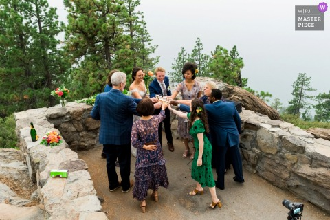 Incline Village, NV image of bride, groom and their family toasting together after an intimate elopement ceremony at the top of a mountain overlook shrouded in wildfire smoke