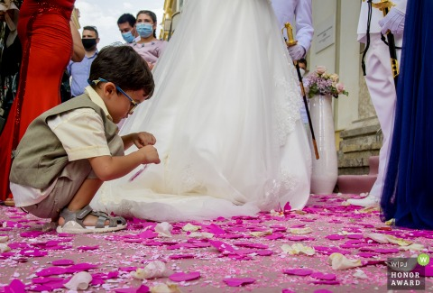 Spain church exit image of a young boy picking up confetti off the ground sitting beside the bride