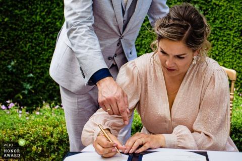 Nederlandse trouwfoto van een vrouw die controleert of de handtekening correct op de huwelijkspapieren staat