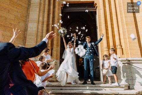 Auvergne-Rhône-Alpes wedding image showing the Exit from the church of the bride and groom with spray of petals