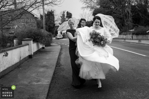 Outdoor rainy wedding photo from Ashbourne showing The bride is going to the church during Jorge storm