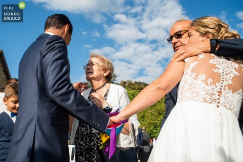 Outdoor France wedding photo from Domaine de la Chesney, Pressagny-l'Orgueilleux during a moment of emotional hugs after the ceremony