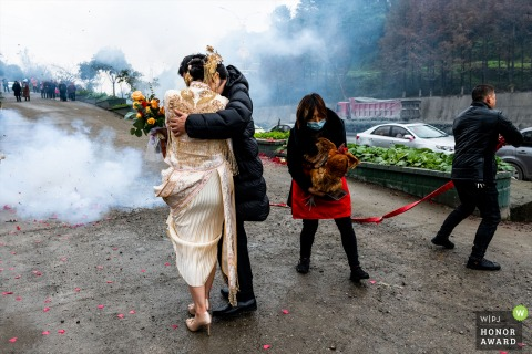 Sichuan wedding photography from When the newlyweds arrive at the bridegroom's home, the bridegroom's mother needs to walk around the couple three times with a rooster, On the far right is the groom's father, He holds one end of the firecrackers