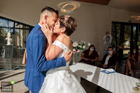 French wedding photography from Castelneau le Lez Town Hall showing The bride and groom kiss after exchanging their vows and rings