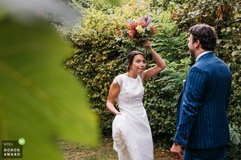Antwerpen outdoor, garden wedding photo from Flanders at the bride and groom's house showing the bride is taking shelter under her bouquet