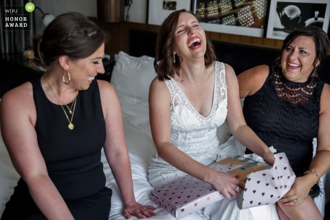 Illinois wedding photo of a Chicago bride opening a gift on a bed during the getting ready