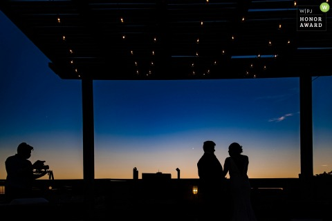 Illinois wedding reception photo at night showing a Chicago couple chatting on the roof