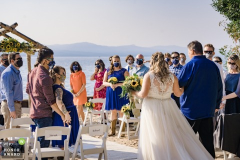California outdoor, lakeside wedding photo from the Tahoe Ceremony Location showing Father of the bride walking her down the aisle while guests wear masks during Covid-19