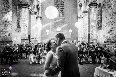 Wedding photo from Oude Kerk, Dongen - the kiss during the ceremony, the wedding guests in the background