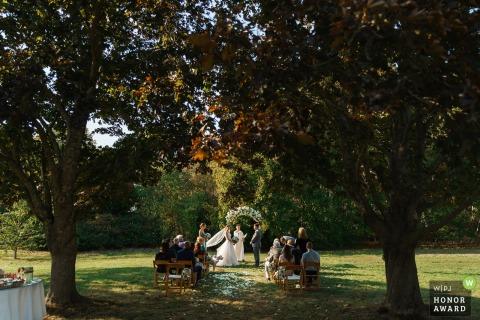 Foto de casamento ao ar livre em Massachusetts sob as árvores nesta cerimônia em Pocasset, Cape Cod, MA