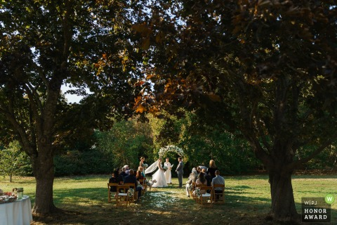 Foto de boda al aire libre de Massachusetts bajo los árboles en esta ceremonia de Pocasset, Cape Cod, MA