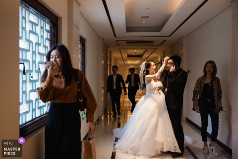 Wedding photo from Hangzhou, China. Hotel While the groom was busy answering the phone, the bride helped the groom trim his hair.