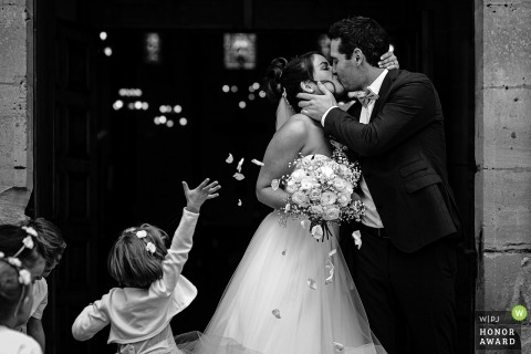 Lyon church wedding photo from Auvergne-Rhône-Alpes after the ceremony bride and groom kiss at the end of the church with the hand of a little girl who throws petals
