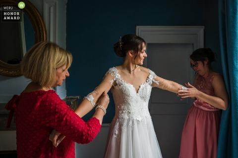 Photographie de mariage à Lyon d'Auvergne-Rhône-Alpes à l'hôtel montrant La mariée se prépare avec un peu d'aide