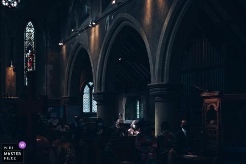 La photographie de reportage de mariage en Angleterre de St Marys Meppershall, Hertfordshire d'un invité dans un peu éclairé dans une église portant un masque en prenant un verre