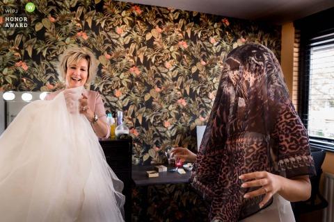 NL trouwfoto Thuis bij het ouderlijk huis van de bruid als ze klaar is om in haar jurk te duiken terwijl ze haar haar beschermt