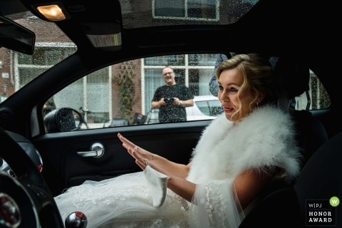 Utrecht wedding photograph from In the car of the bridal couple when The bride is nervous and checking if her hands are shaking, with a face mask with her
