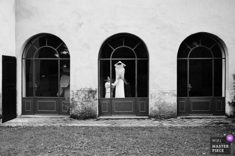Italy wedding photography in black and white from Villa Caproni, Vizzola Ticino of the Getting ready with brides dress hanging in a window