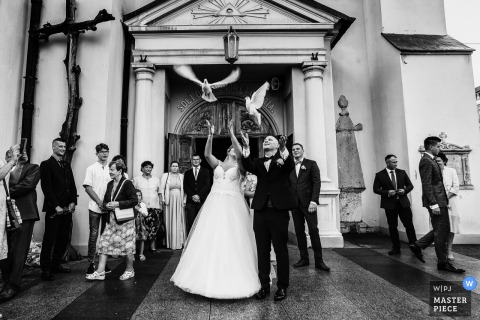 Wedding photography from Andrespol Wedding Hall, Poland - the wedding couple releases the birds after they leave the church
