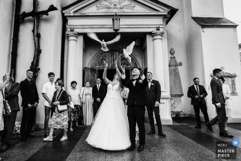 Huwelijksfotografie uit Andrespol Wedding Hall, Polen - het bruidspaar laat de vogels los nadat ze de kerk hebben verlaten
