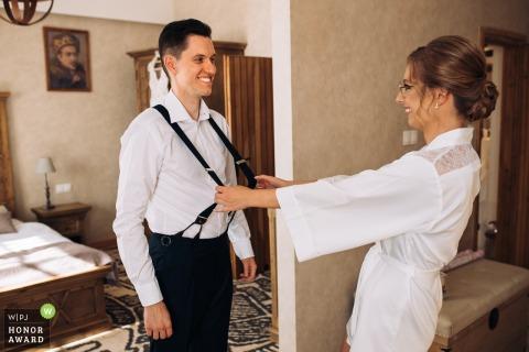 PL trouwfoto van Best Western Podklasztorze Sulejow, Polen waarop het paar te zien is tijdens de voorbereidingen in een hotelkamer.