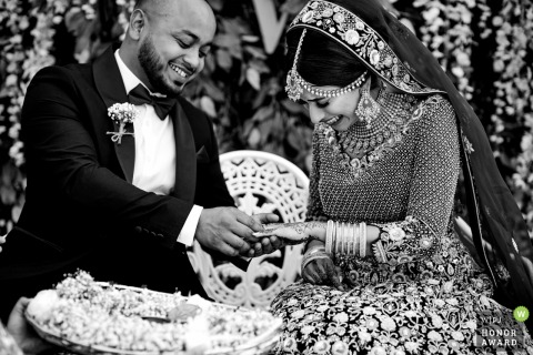 UK wedding reportage photo from Birmingham showing A very happy bride receives a wedding ring from the groom