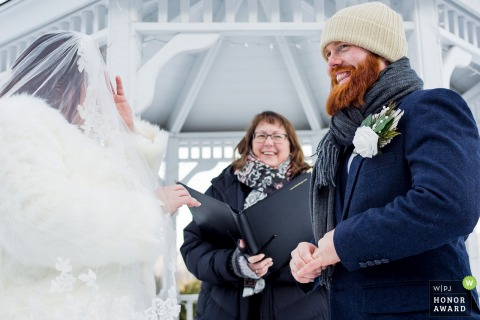 Outdoor winter wedding photo from Jackson, New Hampshire as they are Trying to get that ring onto a nervous swollen finger